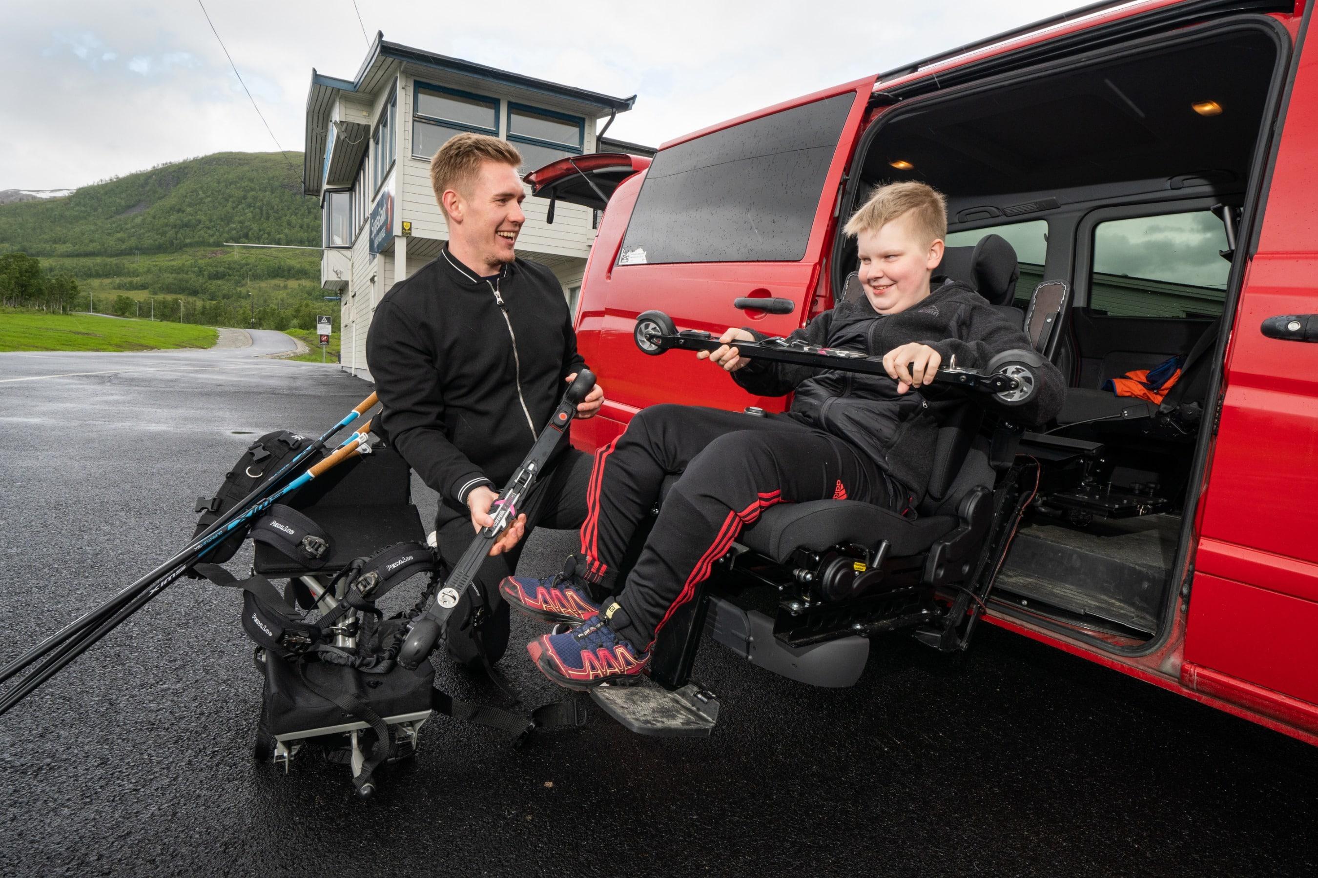 BPA-assistent hjelper bruker i rullestol fra transport til aktivitet med rulleski-kjelke.